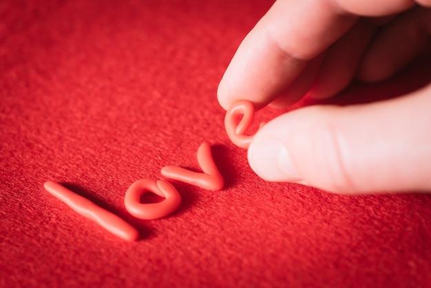 Mężczyzna napisał słowo miłość czerwonymi literami na czerwonym stole na walentynki