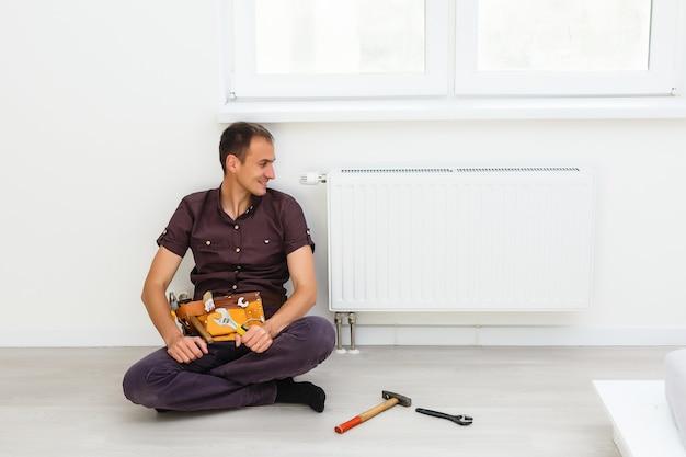 Mężczyzna naprawia baterię chłodnicy w pokoju. prace remontowo-remontowe remontowe w mieszkaniu. renowacja ogrzewania. klucz w rękach