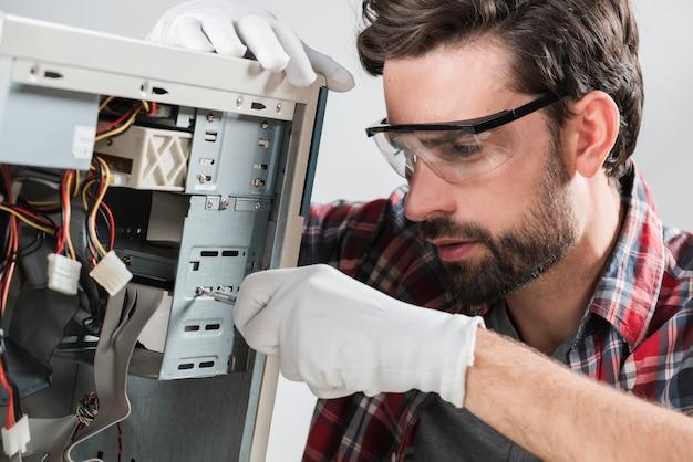 Mężczyzna naprawia cpu z śrubokrętem