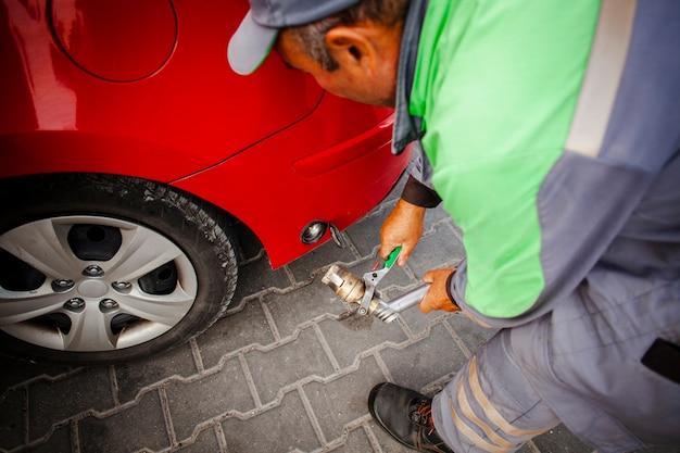 Mężczyzna naprawia czerwonego samochód
