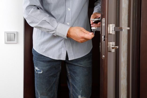 Mężczyzna naprawia klamkę. zbliżenie rąk pracownika instalującego nową szafkę do drzwi