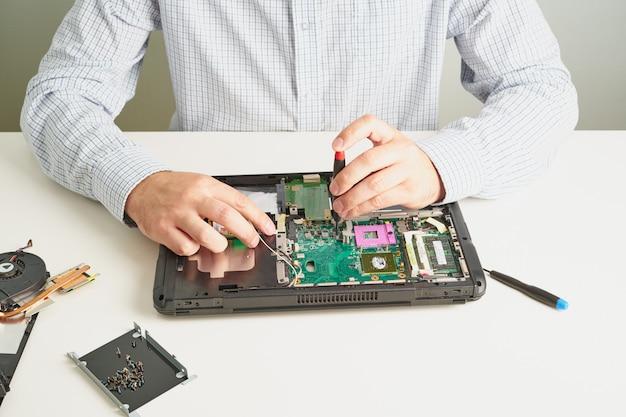 Mężczyzna naprawia komputer. inżynier serwisowy w koszuli naprawia laptopa, przy białym biurku na białej ścianie.