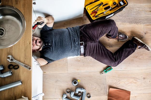 Mężczyzna naprawia kuchennego zlew