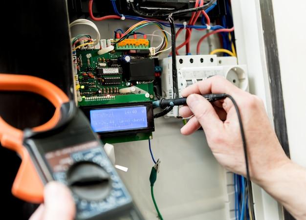 Mężczyzna naprawia napięcie w centrali za pomocą automatycznych przełączników.