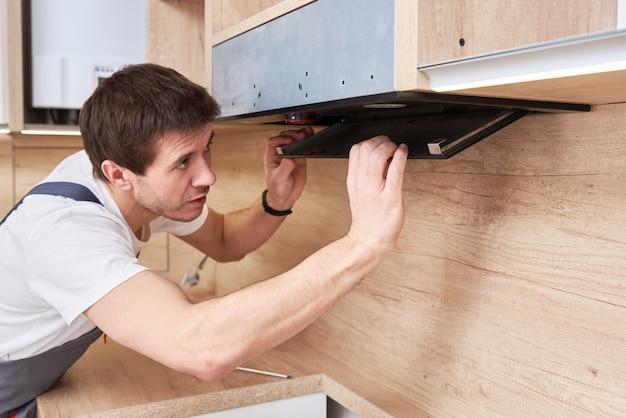 Mężczyzna naprawia okap w kuchni. wymienny filtr w okapie kuchennym