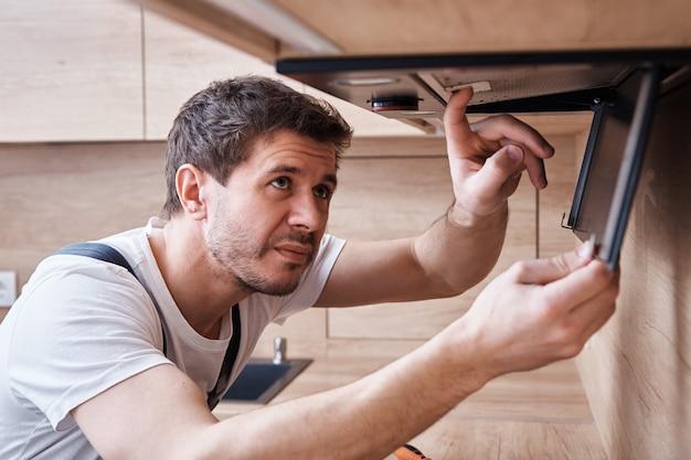 Mężczyzna naprawia okap w kuchni