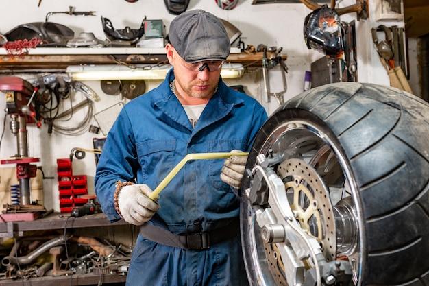 Mężczyzna naprawia opon motocyklowych z zestawem naprawczym