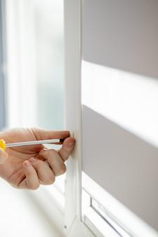 Mężczyzna naprawia plastikowe okno.