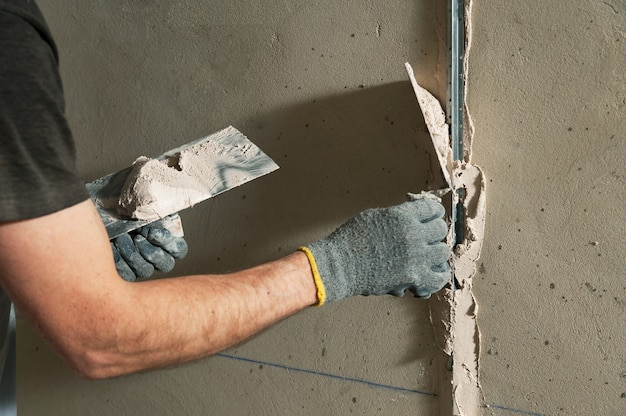 Mężczyzna naprawia przewodnik, aby w przyszłości wyrównać ściany sztukaterią