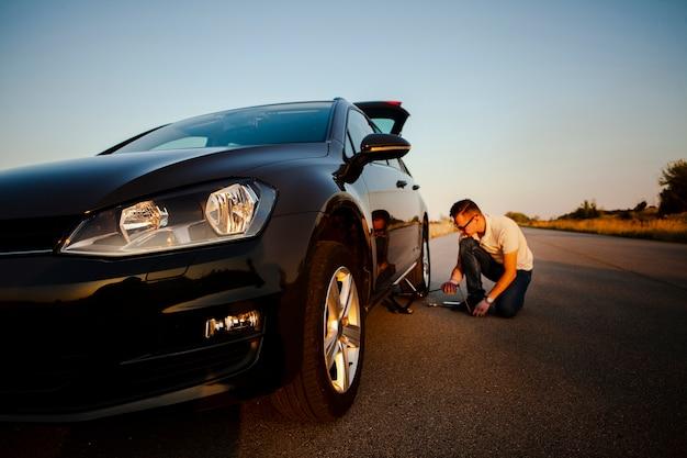 Mężczyzna naprawia samochód