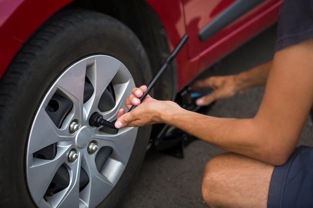 Mężczyzna naprawia samochodowego koło na drodze