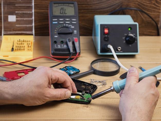 Mężczyzna naprawia telefon komórkowego z lutowniczym żelazem.