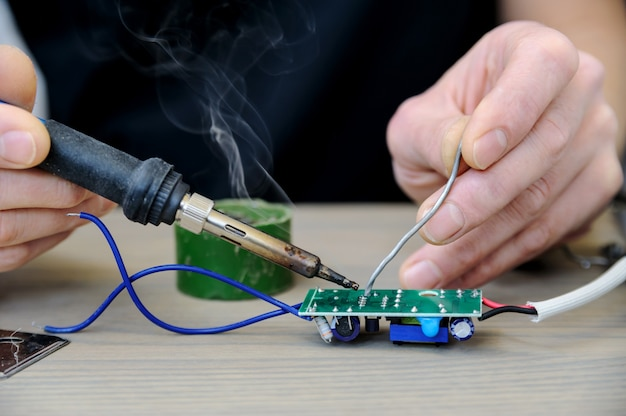 Mężczyzna naprawia zasilacz lampy. trzyma płytkę elektroniczną i lutownicę.