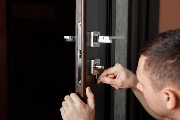 Mężczyzna naprawiający klamkę. stolarz pracujący przy montażu zamka bez klamek do drzwi drewnianych