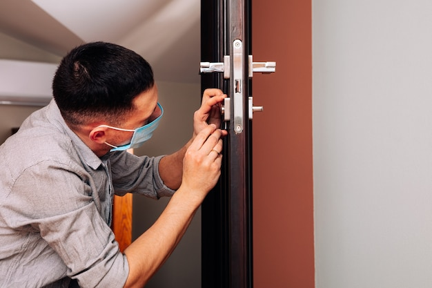 Mężczyzna naprawiający klamkę. zbliżenie rąk pracownika instalującego nową szafkę w drzwiach