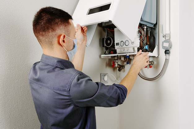 Mężczyzna naprawiający kocioł w masce medycznej