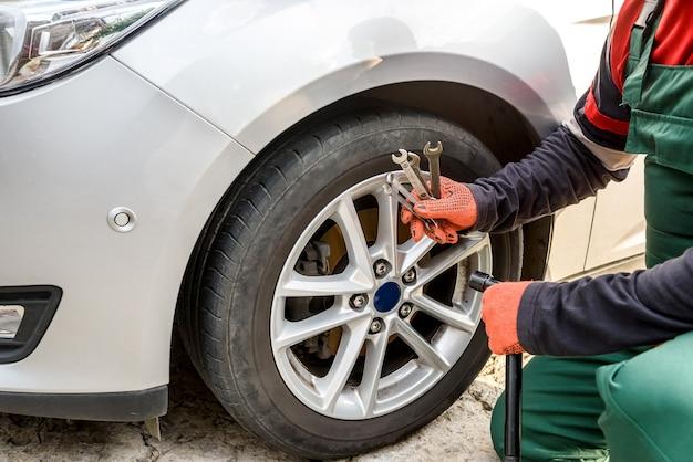 Mężczyzna naprawiający koło samochodowe z kluczem z bliska