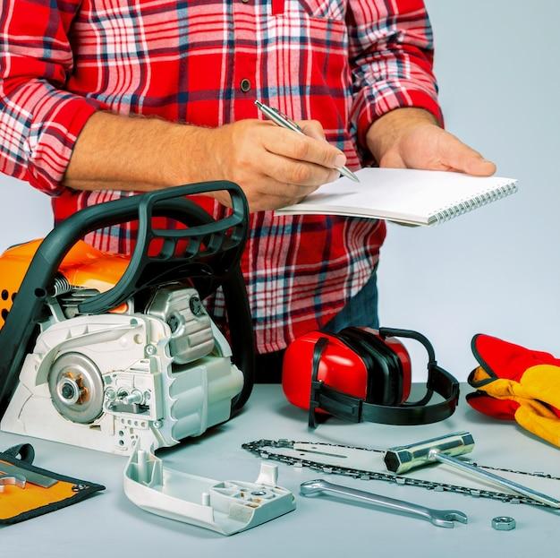 Mężczyzna naprawiający piłę łańcuchową w warsztacie. robotnik trzymający nootbook i długopis. cennik naprawy piły łańcuchowej. mały biznes.