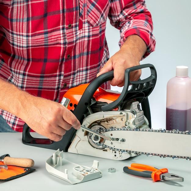 Mężczyzna naprawiający piłę łańcuchową w warsztacie