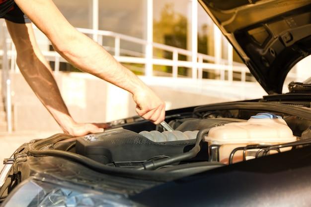 Mężczyzna naprawiający silnik. kontrola samochodu. praca mechanika