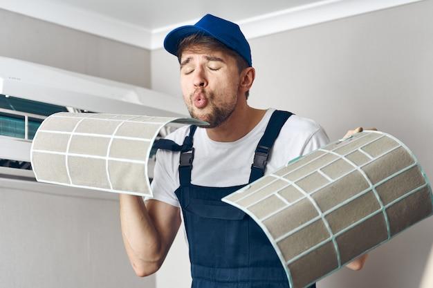Mężczyzna naprawy i czyszczenia klimatyzator, pracownik w domu