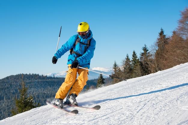 Mężczyzna narciarz jedzie na stoku w piękny słoneczny zimowy dzień w ośrodku zimowym