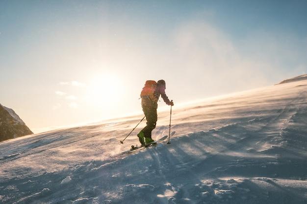 Mężczyzna narciarz z plecakiem trekking na śniegu góry z światłem słonecznym