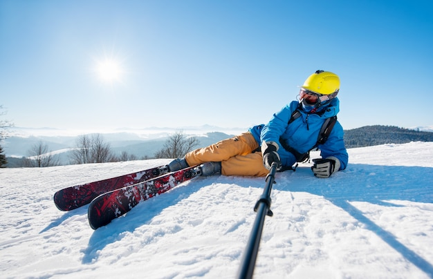 Mężczyzna narciarz za pomocą selfie stick robienia zdjęć podczas jazdy na nartach