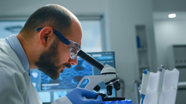 Mężczyzna naukowiec badający próbki pod mikroskopem w nowocześnie wyposażonym laboratorium