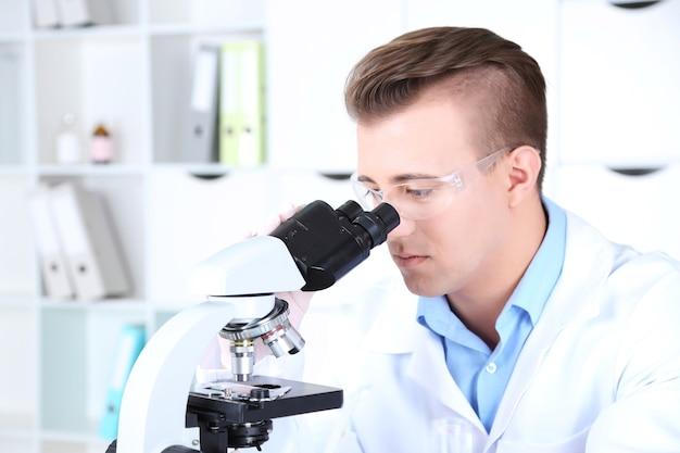 Mężczyzna naukowiec przy użyciu mikroskopu w laboratorium