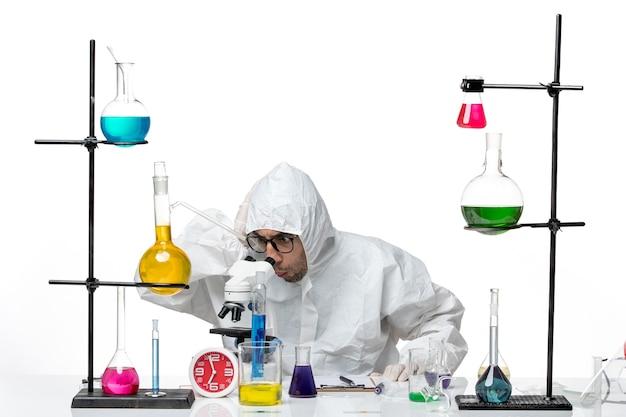 Mężczyzna naukowiec widok z przodu w specjalnym kombinezonie ochronnym przy użyciu mikroskopu