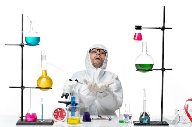 Mężczyzna naukowiec widok z przodu w specjalnym kombinezonie ochronnym, siedzący wokół biurka z rozwiązaniami