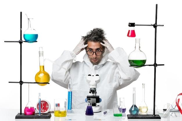 Mężczyzna naukowiec widok z przodu w specjalnym kombinezonie ochronnym, siedzący wokół stołu z rozwiązaniami