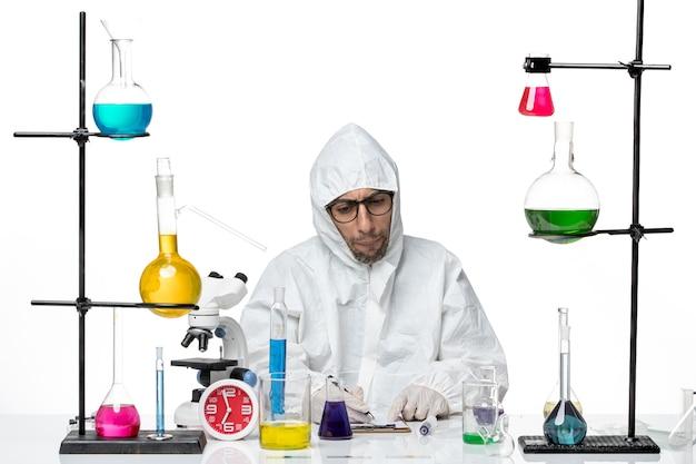 Mężczyzna naukowiec z przodu w specjalnym kombinezonie ochronnym pracujący z roztworami
