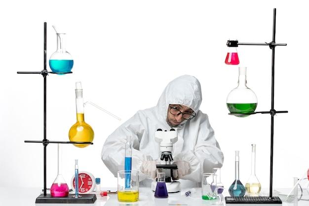 Mężczyzna naukowiec z przodu w specjalnym mikroskopie do mocowania kombinezonu ochronnego