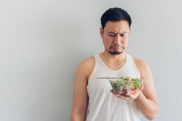 Mężczyzna nienawidzi zdrowego posiłku sałatkowego.