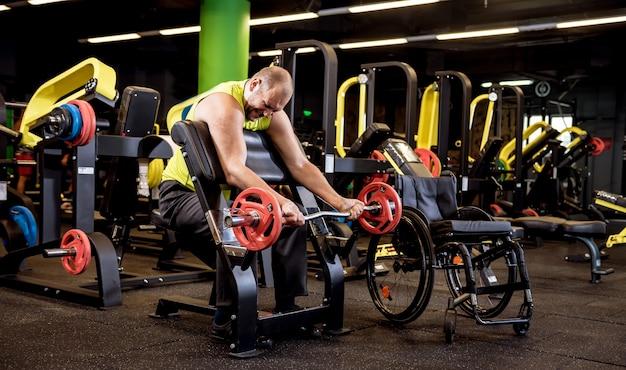 Mężczyzna niepełnosprawny trenujący na siłowni ośrodka rehabilitacji.