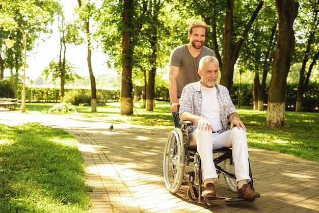 Mężczyzna niesie jego uśmiechniętego ojca na wózku inwalidzkim.