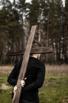 Mężczyzna niesie krzyż. wnieście krzyż. człowiek wierzy w boga. nadzieja w bogu.