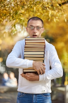 Mężczyzna niesie w rękach wiele książek stos podręczników do szkolenia przygotowanie do egzaminu