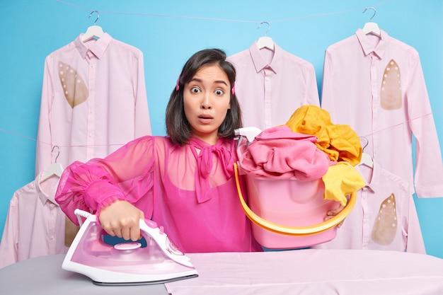 Mężczyzna niesie wiadro pełne wypranego prania używa elektrycznego żelazka parowego pozuje przy desce do prasowania ma wiele obowiązków