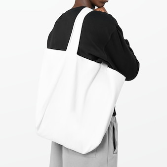 Mężczyzna niosący białą torbę na zakupy wielokrotnego użytku
