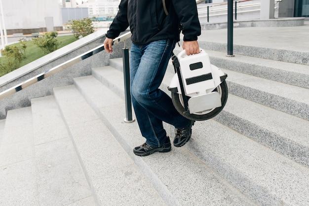 Mężczyzna niosący elektryczny monocykl na ulicy miasta. mobilny przenośny pojazd do transportu indywidualnego. człowiek na jednym kole elektrycznym jadący szybko (euc) do pracy