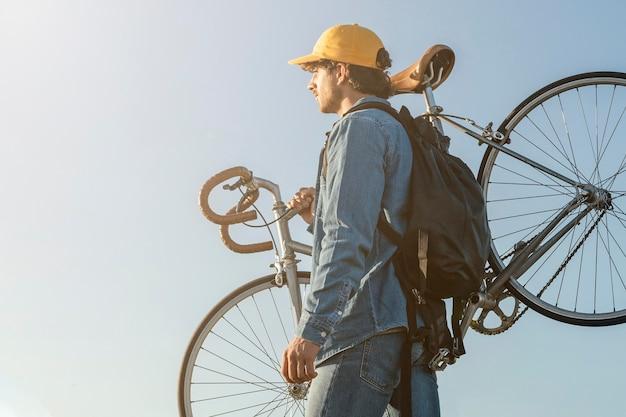 Mężczyzna niosący rower średni strzał