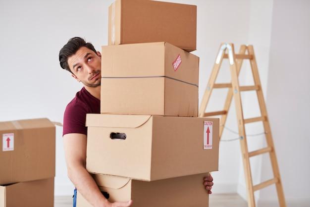 Mężczyzna niosący stos ciężkich kartonów