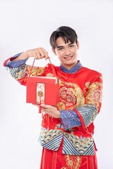 Mężczyzna nosi cheongsam, gotowy dać siostrze czerwoną torbę za niespodziankę w tradycyjny dzień