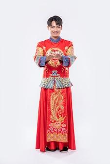 Mężczyzna nosi garnitur w stylu cheongsam i czarny uśmiech buta o dać pieniądze na prezent swojej rodzinie