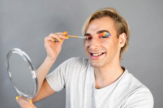 Mężczyzna nosi kosmetyki do makijażu i jest szczęśliwy