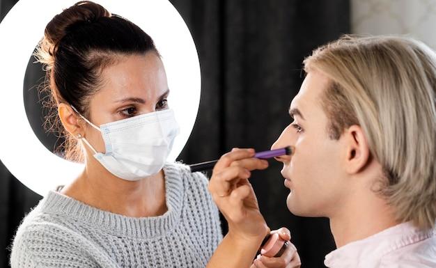 Mężczyzna nosi makijaż i kobieta ma na sobie maskę