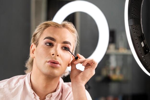 Mężczyzna nosi makijaż za pomocą pędzla do tuszu do rzęs